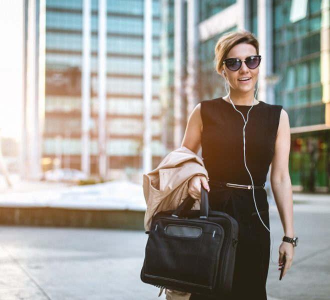 Elegant strong business woman is walking in business district and using phone . She is 34 years old young CEO of company. She is happy and relaxed talking on her phone with headset